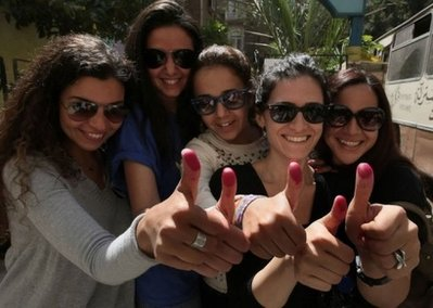 Egyptian women show off ink-stained thumbs after voting